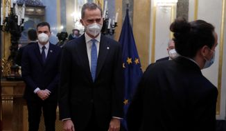 Spain's King Felipe, centre, smiles after greeting Spain's second deputy Prime Minister Pablo Iglesias, right as Spain's Premier Pedro Sanchez, left, looks on inside the Spanish parliament, Madrid, Tuesday Feb. 23, 2021. King Felipe VI, Spanish lawmakers and others are marking 40 years since a paramilitary coup attempt failed to derail the country's peaceful transition to democracy. The anniversary has been obscured by the absence of Juan Carlos I, the former monarch now beset by financial scandals. A ceremony in the Spanish Parliament building, targeted by the coup attempt perpetrators in 1981, has been also boycotted by seven of the parliament's 17 political groups over the monarch's presence. (Juan Carlos Hidalgo, Pool photo via AP)