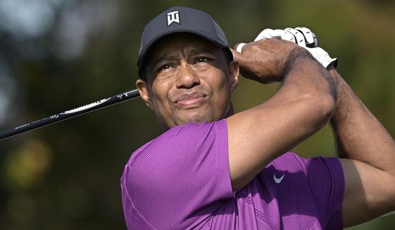 """FILE - Tiger Woods watches his tee shot on the first hole during the first round of the PNC Championship golf tournament in Orlando, Fla., in this Dec. 19, 2020, file photo. Woods was injured Tuesday, Feb. 23, 2021, in a vehicle rollover in Los Angeles County and had to be extricated from the vehicle with the """"jaws of life"""" tools, the Los Angeles County Sheriff's Department said.(AP Photo/Phelan M. Ebenhack, File)"""
