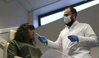Dr. Clair Vandersteen, right, wafts a tube of odors under the nose of a patient, Gabriella Forgione, during tests in a hospital in Nice, southern France, Monday, Feb. 8, 2021, to help determine why she has been unable to smell or taste since she contracted COVID-19 in November 2020. (AP Photo/John Leicester)