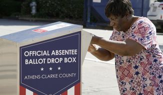 In this Oct. 19, 2020, file photo, a voter drops their ballot off during early voting in Athens, Ga. After record turnout led to stunning GOP losses in the once reliably red state, Republican lawmakers are forging ahead with an aggressive slate of voting legislation that critics argue is tailored toward curtailing the power of Black voters. (AP Photo/John Bazemore) ** FILE **
