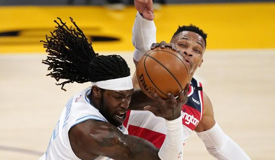 Los Angeles Lakers center Montrezl Harrell, left, grabs a loose ball away from Washington Wizards guard Russell Westbrook during the first half of an NBA basketball game Monday, Feb. 22, 2021, in Los Angeles. (AP Photo/Mark J. Terrill)