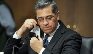 Xavier Becerra removes his mask to make an opening statement during a Senate Finance Committee hearing on his nomination to be secretary of Health and Human Services on Capitol Hill in Washington, Wednesday, Feb. 24, 2021. (Greg Nash/Pool via AP)