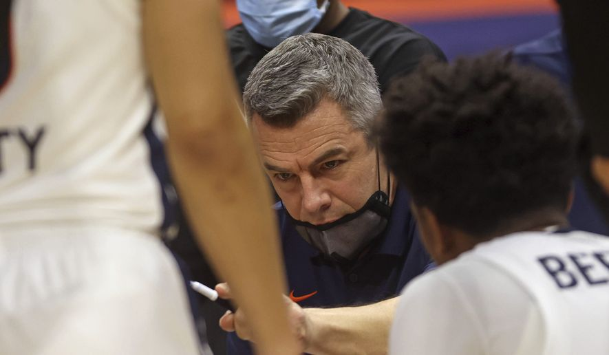 Virginia coach Tony Bennett talks with his players in a huddle during the team's NCAA college basketball game against North Carolina State on Wednesday, Feb. 24, 2021, in Charlottesville, Va. (Andrew Shurtleff/The Daily Progress via AP, Pool)