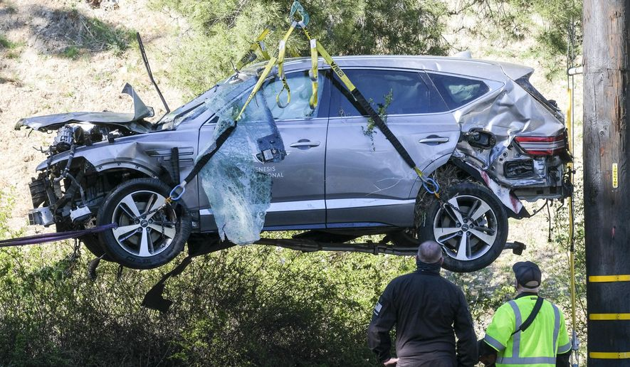A crane is used to lift a vehicle following a rollover accident involving golfer Tiger Woods, Tuesday, Feb. 23, 2021, in the Rancho Palos Verdes suburb of Los Angeles. Woods suffered leg injuries in the one-car accident and was undergoing surgery, authorities and his manager said. (AP Photo/Ringo H.W. Chiu) **FILE**