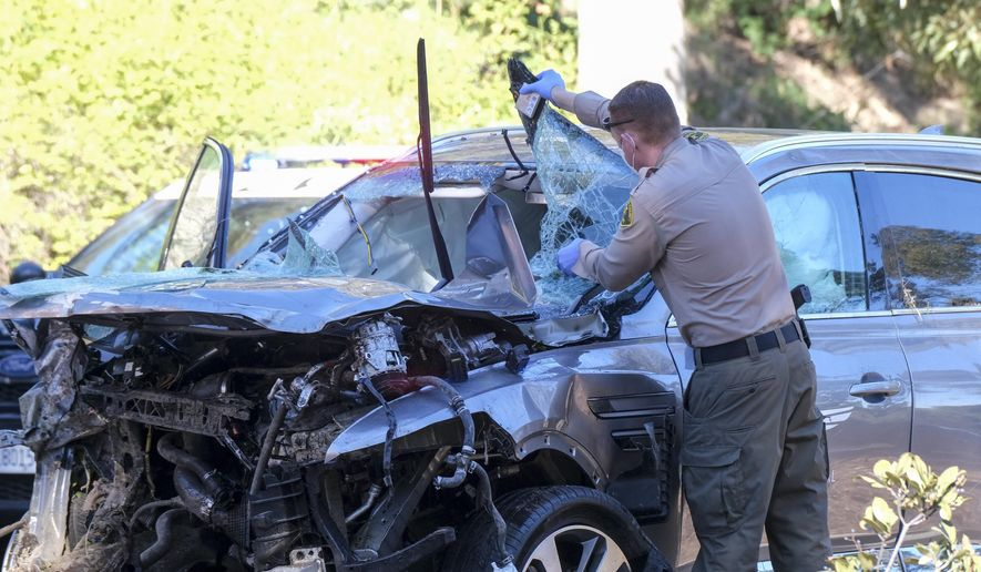 A law enforcement officer looks over a damaged vehicle following a rollover accident involving golfer Tiger Woods, Tuesday, Feb. 23, 2021, in the Rancho Palos Verdes suburb of Los Angeles. Woods suffered leg injuries in the one-car accident and was undergoing surgery, authorities and his manager said. (AP Photo/Ringo H.W. Chiu) **FILE**