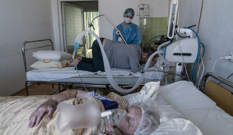 An elderly woman suffering from COVID-19 breathes with the help of an oxygen mask, foreground, as a nurse treats a patient in central district hospital of Kolomyia, western Ukraine, Tuesday, Feb. 23, 2021. After several delays, Ukraine finally received 500,000 doses of the AstraZeneca vaccine marketed under the name CoviShield, the first shipment of Covid-19 vaccine doses. The country of 40 million is one of the last in the region to begin inoculating its population. (AP Photo/Evgeniy Maloletka)