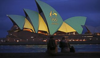 FILE - In this Friday, Aug. 5, 2016, file photo, a couple sit on a dock to look at the sails of the Sydney Opera House that are illuminated with the green and gold colors of the Australian Olympic team. An Australian push to host the 2032 Olympics was elevated overnight to the status of preferred bid, and the people of Brisbane and southeast Queensland state woke up to the news Thursday, Feb. 25, 2021. (AP Photo/Rick Rycroft, File)