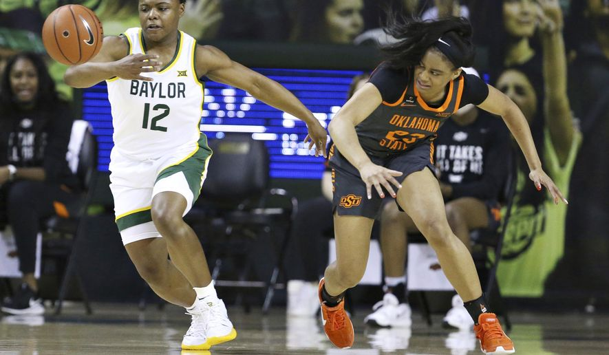 Baylor guard Moon Ursin, left, reaches for a loose ball with Oklahoma State guard Lauren Fields, right, in the first half of an NCAA college basketball game, Wednesday, Feb. 24, 2021, in Waco, Texas. (Rod Aydelotte/Waco Tribune Herald via AP)