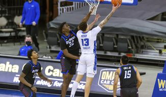 Creighton forward Christian Bishop (13) makes a layup against DePaul forward David Jones (32) in the first half during an NCAA college basketball game Wednesday, Feb. 24, 2021, in Omaha, Neb. (AP Photo/John Peterson)