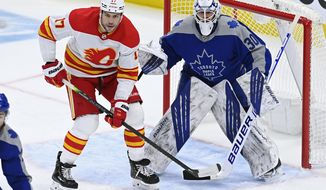 Calgary Flames left wing Milan Lucic (17) and Toronto Maple Leafs goaltender Michael Hutchinson (30) watch the play during first period NHL action in Toronto on Wednesday, Feb. 24, 2021. (Frank Gunn/The Canadian Press via AP)