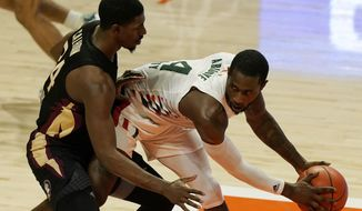 Miami guard Elijah Olaniyi (4) looks to pass the ball as Florida State guard Sardaar Calhoun (24) defends during the second half of an NCAA college basketball game, Wednesday, Feb. 24, 2021, in Coral Gables, Fla. (AP Photo/Marta Lavandier)