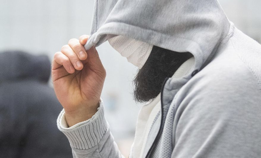 A man who calls himfelf Abu Walaa, alleged leader of the terrorist militia Islamic State (IS) in Germany, hides his face at the Higher Regional Court in Celle, Germany, Wednesday, Feb. 24, 2021. The state court in Celle in northern Germany convicted the 37-year-old Iraqi citizen who goes by the alias Abu Walaa of membership in and support for a terrorist organization. (Julian Stratenschulte/DPA via AP, Pool)