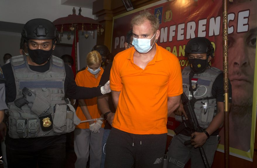 Indonesian police officers escorted Andrei Kovalenka, center, and his partner Ekaterina Trubkina, walks behind during a news conference at immigration office in Jimbaran, Bali, Indonesia on Wednesday, Feb. 24, 2021. Kovalenka, a Russian listed by the Interpol as a fugitive back home was arrested on the Indonesian tourist island of Bali on Wednesday after 13 days on the run with his partner to avoid deportation. (AP Photo/Firdia Lisnawati)