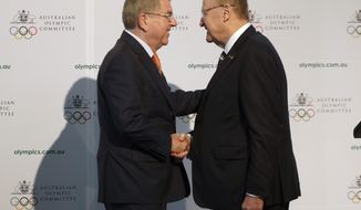 """FILE - In this Saturday, May 4, 2019 file photo, International Olympic Committee President Thomas Bach, left, shakes hands with Australian Olympic Committee (AOC) President John Coates at the AOC annual general meeting in Sydney, Australia.  The Australian Olympic bid is on a fast-track to host the 2032 Olympics Wednesday Feb. 24, 2021, after the International Olympic Committee executive board gave Queensland """"preferred bidder"""" status, 11 years ahead of the games.(AP Photo/Rick Rycroft, File)"""