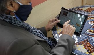 Lynette White uses her tablet while interviewed in San Francisco, Tuesday, Feb. 16, 2021. The pandemic has sparked a surge of online shopping across all ages as people stay away from physical stores. But the biggest growth has come from consumers 65 and older. (AP Photo/Jeff Chiu)