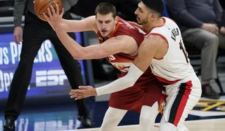 Denver Nuggets center Nikola Jokic, left, is defended by Portland Trail Blazers center Enes Kanter during the second half of an NBA basketball game on Tuesday, Feb. 23, 2021, in Denver. (AP Photo/David Zalubowski)