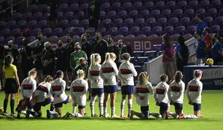Some members of the United States team kneel during the playing of the national anthem before a SheBelieves Cup women's soccer match against Canada, Thursday, Feb. 18, 2021, in Orlando, Fla. (AP Photo/Phelan M. Ebenhack) **FILE**