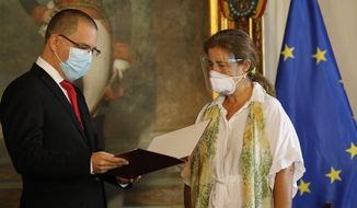 "European Union Ambassador to Venezuela Isabel Brilhante Pedrosa is presented with a letter of ""persona non grata"" from Venezuelan Foreign Minister Jorge Arreaza at his office in Caracas, Venezuela, Wednesday, Feb. 24, 2021. The meeting was called after the EU sanctioned an additional 19 Venezuelans for ""undermining democracy and the rule of law"" in Venezuela and the National Assembly declared the EU ambassador ""persona non grata."" (AP Photo/Ariana Cubillos)"