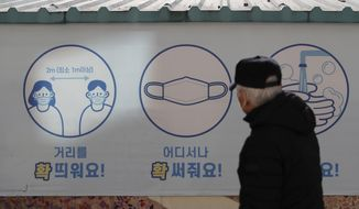 """A man wearing a face mask, looks at a banner displaying precautions against the coronavirus in Goyang, South Korea, Wednesday, Feb. 24, 2021. The letters read """"Mandatory mask wearing."""" (AP Photo/Lee Jin-man)"""