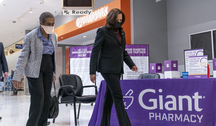 Vice President Kamala Harris, right, accompanied by Delegate Eleanor Holmes Norton, D-D.C., left, arrives to watch a COVID-19 vaccine being administered at a Giant Foods grocery store, Thursday, Feb. 25, 2021, in Washington. (AP Photo/Andrew Harnik)