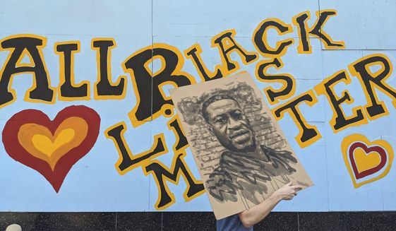 """A demonstrator carries an image of George Floyd in front of a boarded up business decorated with a mural reading """"All Black Lives Matter,"""" on Hollywood Boulevard, during a march organized by black members of the LGBTQ community in the Hollywood section of Los Angeles. The Black Lives Matter Global Network Foundation, which grew out of the creation of the Black Lives Matter movement, is formally expanding a $3 million financial relief fund that it quietly launched in February 2021, to help people struggling to make ends meet during the ongoing coronavirus pandemic. (AP Photo/Damian Dovarganes, File)"""