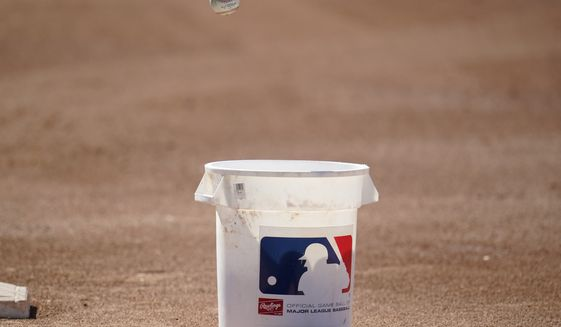 A baseball gets tosses into a bucket during a Chicago White Sox spring training baseball practice Wednesday, Feb. 24, 2021, in Phoenix. (AP Photo/Ross D. Franklin)