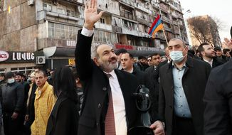 Armenian Prime Minister Nikol Pashinyan waves to supporters during a rally in his support in the center of Yerevan, Armenia, Thursday, Feb. 25, 2021. Armenia's prime minister has spoken of an attempted military coup after facing the military's General Staff demand for him to step down. The developments come after months of protests sparked by the nation's defeat in the Nagorno-Karabakh conflict with Azerbaijan. (Tigran Mehrabyan/PAN Photo via AP)