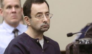 FILE - In this Jan. 24, 2018, file photo, Larry Nassar, a former doctor for USA Gymnastics and member of Michigan State's sports medicine staff, sits in court during his sentencing hearing in Lansing, Mich.  John Geddert, a former U.S. Olympics gymnastics coach, is being charged Thursday, Feb. 25, 2021, with crimes, including sexual assault, human trafficking and running a criminal enterprise is the latest fallout from the sexual abuse scandal involving Nassar. (AP Photo/Carlos Osorio, File)
