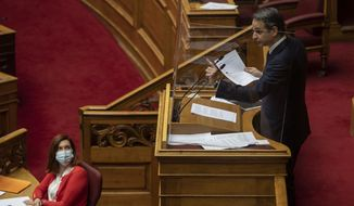Greek Prime Minister Kyriakos Mitsotakis speaks during a parliamentary session in Athens, Thursday, Feb. 25, 2021. Mitsotakis has promised to outline proposed legal changes in parliament on Thursday to make it easier for victims of sexual assault to report the crimes. (AP Photo/Petros Giannakouris)