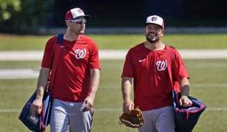 Washington Nationals' Ryan Zimmerman, left, walks toward the clubhouse with teammate Kyle Schwarber at the end of spring training baseball practice Thursday, Feb. 25, 2021, in West Palm Beach, Fla. (AP Photo/Jeff Roberson)