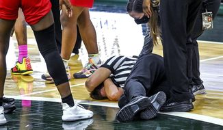 Referee Angie Enlund lies on the court after being inadvertently knocked down by Rutgers' Tekia Mack near the end of an NCAA college basketball game between Rutgers and Michigan State on Wednesday, Feb. 24, 2021, in East Lansing, Mich. (Nick King/Lansing State Journal via AP)