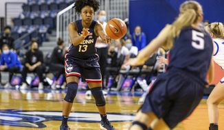 Connecticut guard Christyn Williams (13) makes a pass to guard Paige Bueckers (5) against Creighton in the third quarter during an NCAA college basketball game Thursday, Feb. 25, 2021, in Omaha, Neb. (AP Photo/John Peterson)