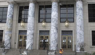 A legislative aide enters the Alaska State Capitol as a worker clears snow from in front of the building on Thursday, Feb. 25, 2021, in Juneau, Alaska. The Alaska House speaker announced on Wednesday, Feb. 24, that a House member had tested positive for COVID-19. (AP Photo/Becky Bohrer)