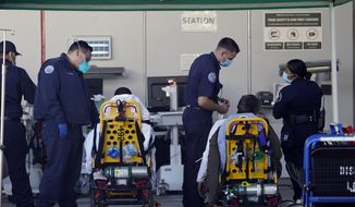 Los Angeles County emergency medical technicians deliver patients for admission at the Ambulatory Care Center station at the MLK Community Medical Group hospital in Los Angeles, Wednesday, Feb. 24, 2021. (AP Photo/Damian Dovarganes)