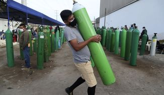 A man carries his empty oxygen tank to be filled after arriving at the head of the line, in the Villa El Salvador neighborhood of Lima, early Thursday morning, Feb. 18, 2021.  A crisis over the supply of medical oxygen for coronavirus patients has struck in Africa and Latin America, where warnings went unheeded at the start of the pandemic and doctors say the shortage has led to unnecessary deaths. (AP Photo/Martin Mejia)