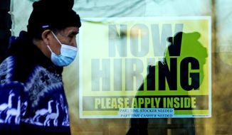 FILE - In this Nov. 28, 2020 file photo, a shopper wears a face mask and he walks past a store displaying a hiring sign in Wheeling, Ill. The number of Americans seeking unemployment benefits fell sharply last week but remained high by historical standards. Applications for benefits declined 111,000 from the previous week to a seasonally adjusted 730,000, the Labor Department said Thursday, Feb. 25. It is the lowest figure since late November.  (AP Photo/Nam Y. Huh, File)