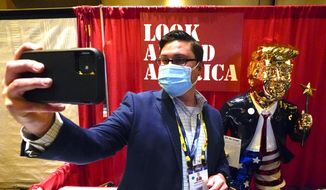 A conference attendee takes a selfie photo in front of a statue of former president Donald Trump at the Conservative Political Action Conference (CPAC) Friday, Feb. 26, 2021, in Orlando, Fla. (AP Photo/John Raoux)