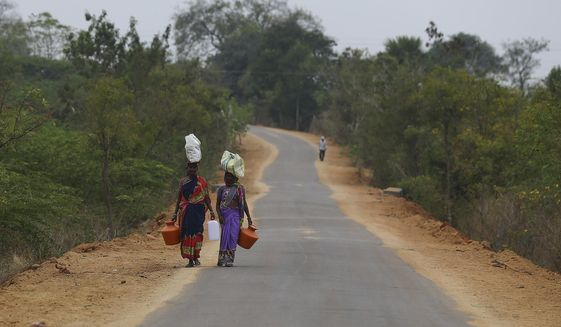 Indian villagers carry their belongings on their heads and walk towards their village on the outskirts of Hyderabad, India, Friday, Feb. 19, 2021. (AP Photo/Mahesh Kumar A.)