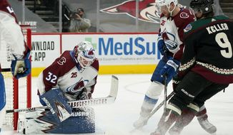 Colorado Avalanche goaltender Hunter Miska (32) makes a save as Arizona Coyotes right wing Clayton Keller (9) and Avalanche defenseman Devon Toews, second from right, look on during the first period of an NHL hockey game Friday, Feb. 26, 2021, in Glendale, Ariz. (AP Photo/Ross D. Franklin)