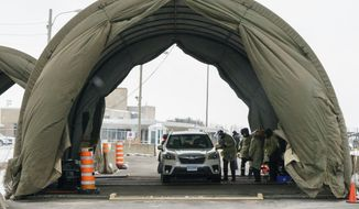 Passengers are screened and get a COVID-19 test as they enter Canada from the United States at the land border crossing in Saint-Bernard-de-Lacolle, Quebec, on Monday, Feb. 22, 2021. (Paul Chiasson/The Canadian Press via AP)