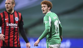Bremen's striker Joshua Sargent reacts after scoring next to Frankfurt's midfielder Sebastian Rode, during the German Bundesliga soccer match between Werder Bremen and Eintracht Frankfurt at Wohninvest Weserstadion in Bremen, Germany, Friday, Feb. 26, 2021. (Carmen Jaspersen/dpa via AP)