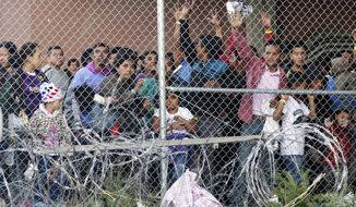 In this March 27, 2019, file photo, Central American migrants wait for food in a pen erected by U.S. Customs and Border Protection to process a surge of migrant families and unaccompanied minors in El Paso, Texas. (AP Photo/Cedar Attanasio, File)