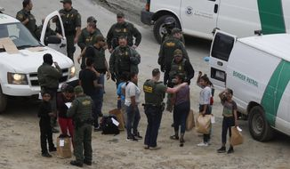 A girl waves to a young man watching from Mexican territory who said he was her cousin, as a group of Honduran asylum seekers is taken into custody by U.S. Border Patrol agents after the group crossed the U.S. border wall into San Diego, California, seen from Tijuana, Mexico. (AP Photo/Rebecca Blackwell, File)