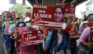 University teachers march with the images of deposed Myanmar leader Aung San Suu Kyi in Yangon, Myanmar, Friday, Feb. 26, 2021. Supporters of Myanmar's junta attacked people protesting the military government that took power in a coup, using slingshots, iron rods and knives Thursday to injure several of the demonstrator (AP Photo) (AP Photo)