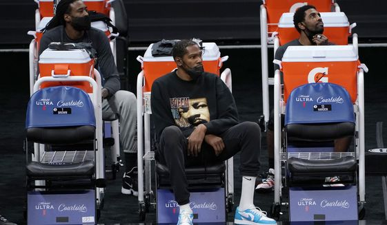 Brooklyn Nets DeAndre Jordan, left, Kevin Durant, center, and Kyrie Irving watch their teammates play the Sacramento King during the second half of an NBA basketball game in Sacramento, Calif., Monday, Feb. 15, 2021. Durant did not play due to an injury. The Nets won 136-125. (AP Photo/Rich Pedroncelli)