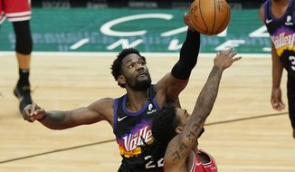 Phoenix Suns center Deandre Ayton, left, blocks a shot by Chicago Bulls guard Coby White during the second half of an NBA basketball game in Chicago, Friday, Feb. 26, 2021. (AP Photo/Nam Y. Huh)