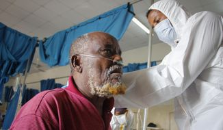 A doctor tends to a patient suffering from COVID-19 in a ward for coronavirus patients at the Martini hospital in Mogadishu, Somalia Wednesday, Feb. 24, 2021. (AP Photo/Farah Abdi Warsameh)
