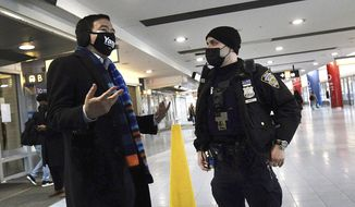 New York mayoral candidate Andrew Yang, left, talks to a New York City Police officer following an incident where Yang intervened as a photographer was attacked on the Staten Island Ferry, Friday, Feb. 26, 2021, in New York. (Paul Liotta/Staten Island Advance via AP)