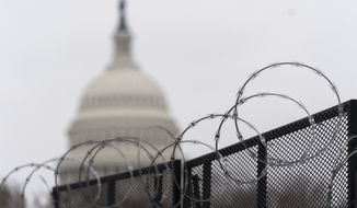 In this Feb. 18, 2021, file photo, the U.S. Capitol is seen behind the razor fence around the U.S. Capitol. (AP Photo/Manuel Balce Ceneta, File)