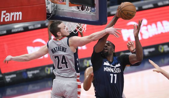 Minnesota Timberwolves center Naz Reid (11) goes to the basket against Washington Wizards guard Garrison Mathews (24) during the second half of an NBA basketball game, Saturday, Feb. 27, 2021, in Washington. (AP Photo/Nick Wass)